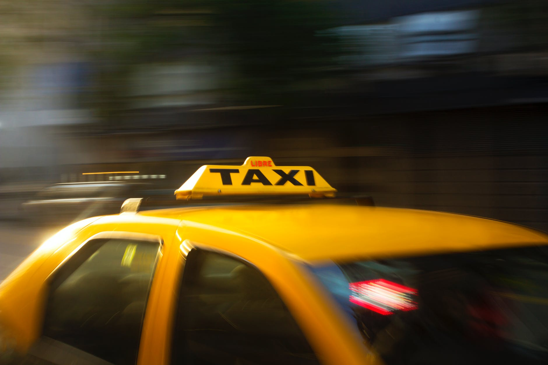 panning photography of yellow taxi